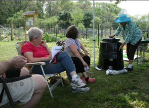 Sustainable Belmont member, Judy Otto demonstrates composting at Rock Meadows Victory Garden.